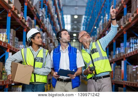 Worker looking up in warehouse while holding digital devices and box