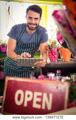 Portrait of male florist holding digital tablet at his flower shop