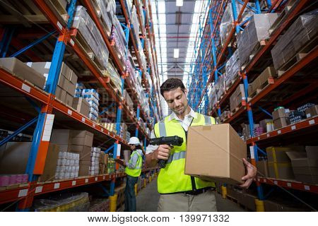 Worker scanning a box in warehouse