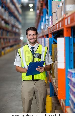 Worker with clipboard looking at camera in warehouse