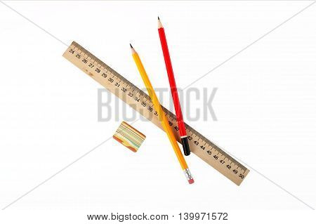 Stationery - Wooden school ruler eraser and two graphite pencils on a white background.