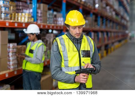 Worker checking stock with digital equipment in warehouse