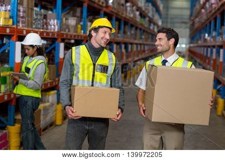 Workers holding box looking each other in warehouse