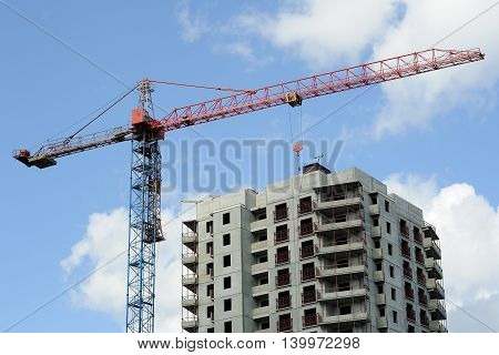 construction of a house. the crane against the background of the cloudy sky