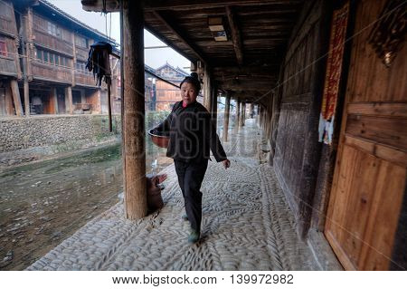 Zhaoxing Dong Village Guizhou Province China - April 9 2010: Asian women rural resident is walking on a paved stone walkway near the river embankment of wooden houses of local farmers.