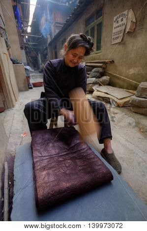 Zhaoxing Dong Village Guizhou Province China - April 9 2010: Dong woman pounding dyed cotton cloth to make it shiny.