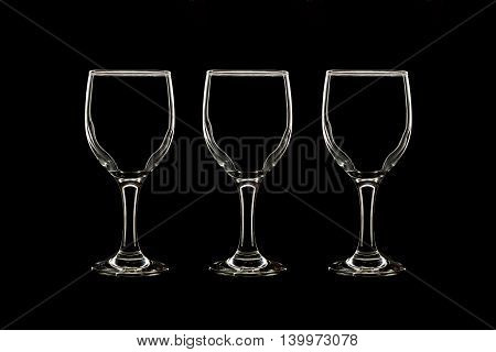 Empty three wine glass isolated on black background