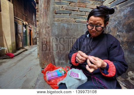 Zhaoxing Dong Village Guizhou Province China - April 9 2010: Mature Asian woman embroiders designs on fabric sitting near the wall of a stone house on a rural street.