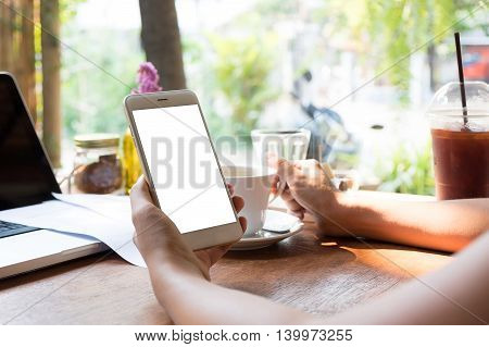 Woman using smart phone with blank mobile and cup of coffee .Smart phone with blank screen and can be add your texts or others on smart phone.