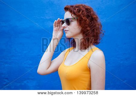 Profile portrait of a ginger girl in sunglasses against blue wall