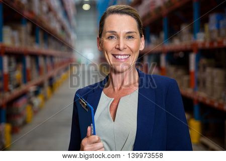 Business woman smiling with her clipboard in a warehouse