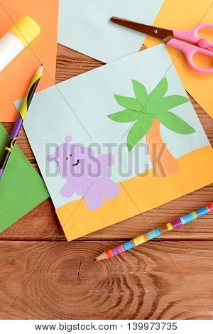 Fun summer card with a hippopotamus and a palm tree on a wooden table. Preschool and kindergarten crafts. Materials for kids art. Paper and glue crafts activity for children. Early child development