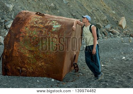 man standing on the beach near a huge rusty buoy