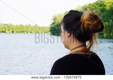 back or rear view of young woman looking over lake
