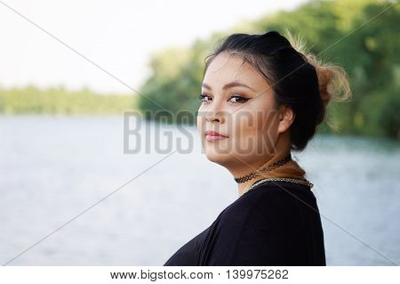 young asian woman standing by the lake