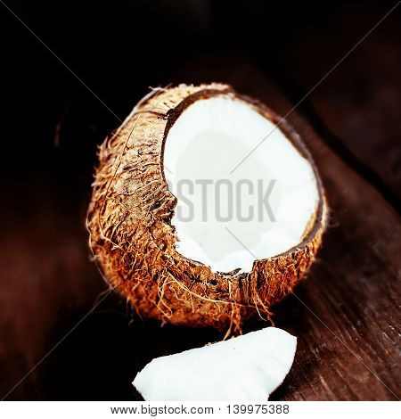 Coconut over dark background. Close up of coco nut on a wooden table with copy space