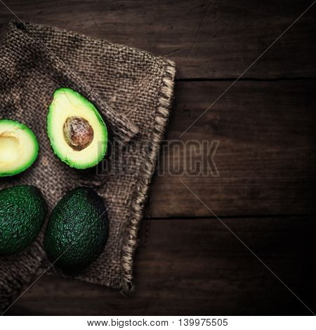 Halved avocado on a rustic table. Fresh avocado palta on black background. Guacamole ingredient top view. Vegetarian or healthy eating.
