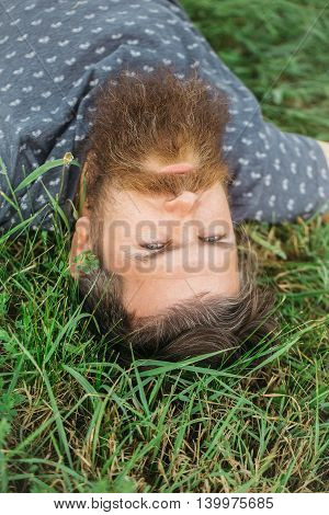 Bearded Man Laying On Green Grass