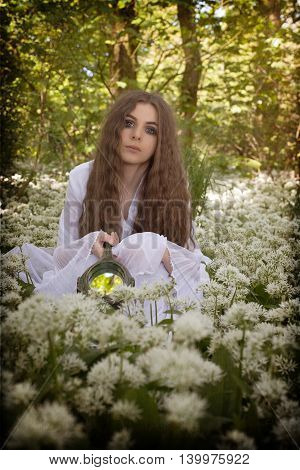 Beautiful Woman Wearing A Long White Dress Sitting In White Flowers