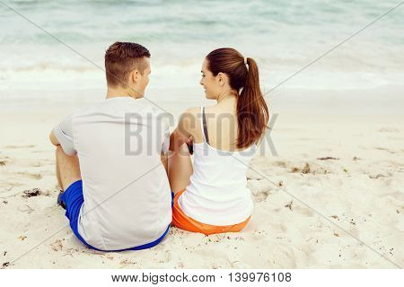 Young couple looking at each other while sitting on beach