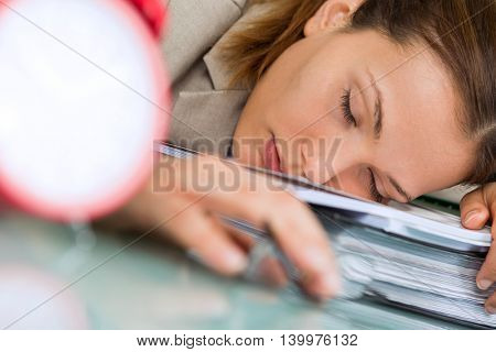 tired young businesswoman sleeping on pile of folders in office
