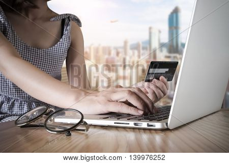 A woman using her credit card with her laptop for Online shoping. vintage filter