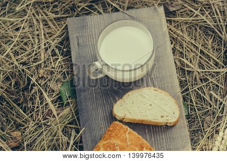 Freshly baked loaf of wheat bread and cut slice on wooden board on straw or hay background with glass cup of milk
