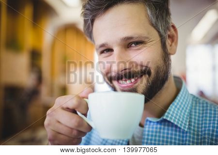 Portrait of happy businessman having coffee at office cafeteria
