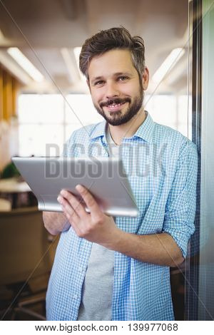 Portrait of young businessman holding digital tablet in office
