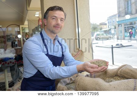 seller holding a scoop of a brown roasted coffee grain