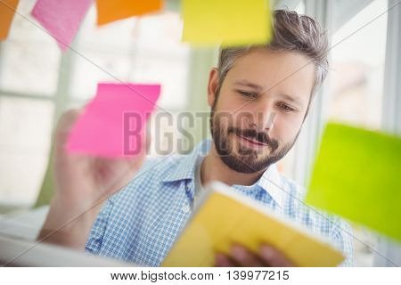 Close-up of businessman writing on adhesive notes at creative office
