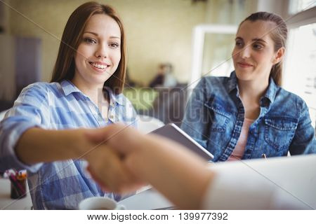 Young businesswomen shaking hands in creative office