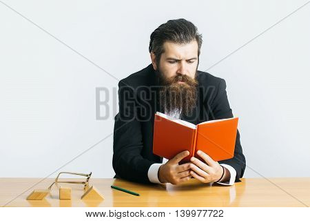 young handsome bearded man scientist or professor with long beard and teacher glasses with red book or notepaper sitting at table with wooden cubes on light background