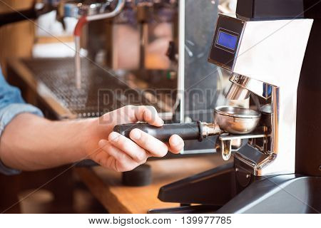 Useful tool. Cropped image of someone holding part of coffee machine with grind coffee beans