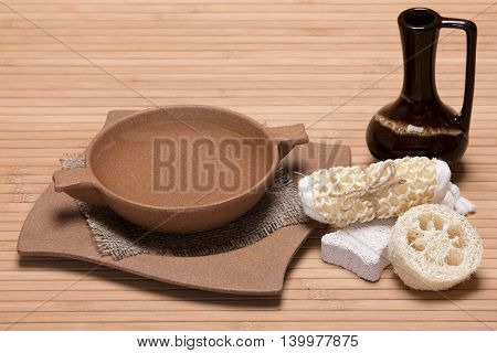 Spa and peeling accessories: pumice, loofah, body scrubber, bamboo plate filled with water, clay jug on wooden surface