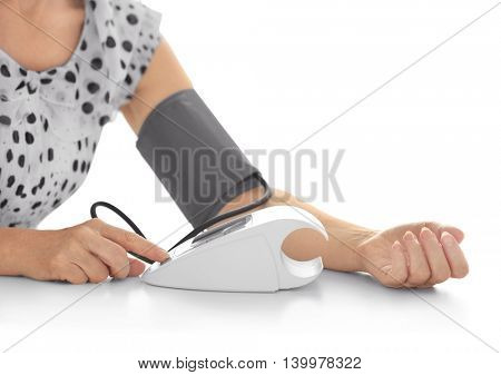 Woman measuring blood pressure with tonometer herself on white background