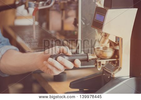Coffee equipment. Cropped image of male barista holding part of coffee machine with grind coffee beans