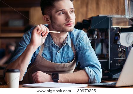 Thoughtful barista. Serious male barista holding pencil and planning his work