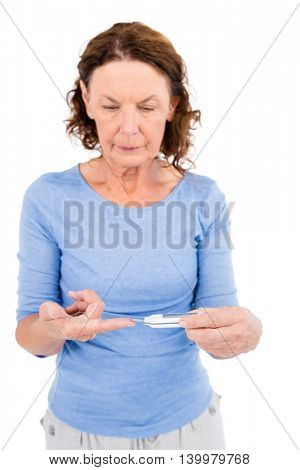 Mature woman using blood glucose monitor against white background