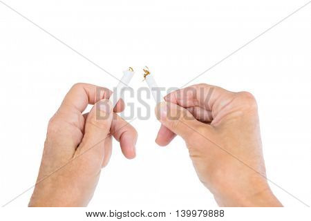 Cropped image of person holding broken cigarette against white background