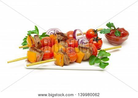 skewers of meat with vegetables on a white background. horizontal photo.