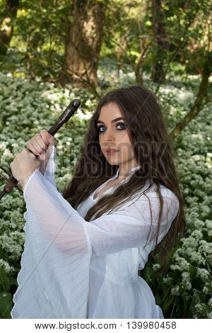 Beautiful Young Woman In A Forest Holding A Sword