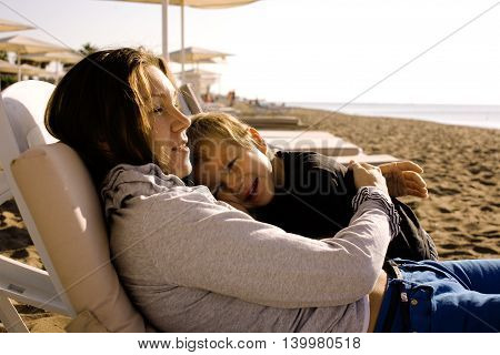 young mother with son resting on sea coast, happy family together talking, lifestyle people concept