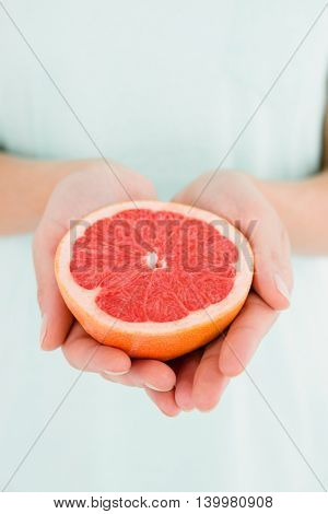 Midsection of woman holding grapefruit