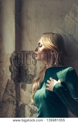 young pretty woman with long lush curly blonde hair and thoughtful face in green dress standing near stony wall