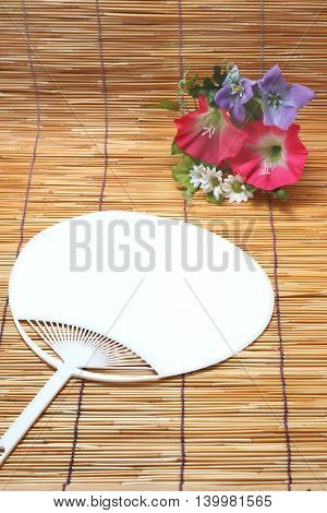 Morning glory and fan on bamboo blind. Japanese summer concept.