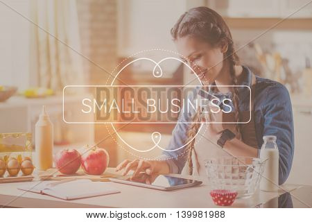 Online payment. Inspirational typographic quote of small business with smiling young woman buying something online with help of tablet computer and credit card in a background