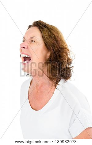 Angry mature woman shouting while standing against white background
