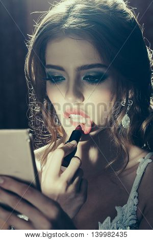 Young woman with beautiful face doing makeup with red lipstick in beauty salon holding mirror
