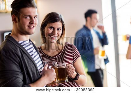 Portrait of happy young couple with beer mug in restaurant
